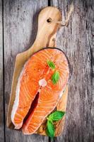 bife de salmão cru fresco com manjericão na tábua foto