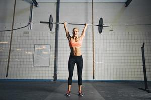 jovem mulher forte fazendo levantamento de peso foto