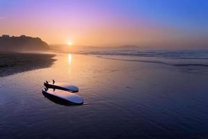 praia de sopelana com pranchas de surf na costa foto