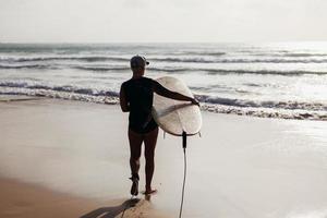 mulher de surf com prancha de surf vista traseira