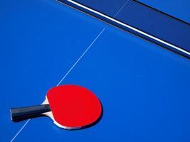 mesa de tênis azul e taco de ping pong vermelho