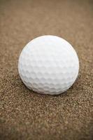 bola de golfe na armadilha de areia vertical foto
