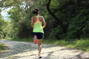 atleta corredor correndo na trilha da floresta. foto