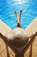 mulher sentada à beira da piscina