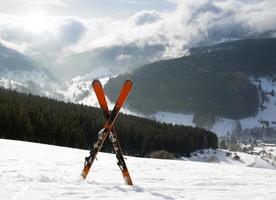 par de esquis cruzados na neve, altas montanhas foto
