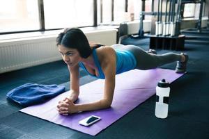 jovem mulher fazendo exercícios de ioga na esteira da ioga foto