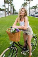 jovem ciclista feminina encantadora posando com sua bicicleta vintage ao ar livre foto