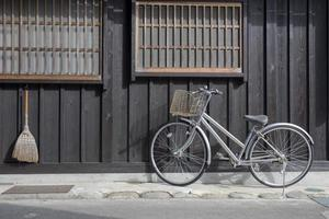 bicicleta e vassoura na frente da antiga casa de japão foto