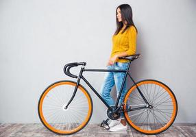 mulher sorridente em pé perto de bicicleta
