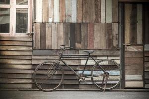 pé de bicicleta vintage perto de uma parede de madeira vintage foto
