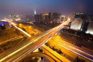 trilhas de semáforo no viaduto e paisagem urbana à noite foto