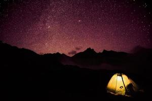 barraca brilhante nas montanhas e estrelas foto