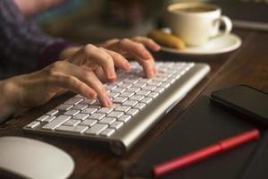 trabalhador de escritório feminino digitando no teclado do computador. foto