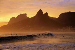 surfando na praia de ipanema em um pôr do sol