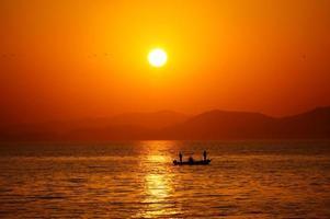 pôr do sol com pescador foto