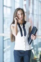 empresária no celular, segurando a pasta