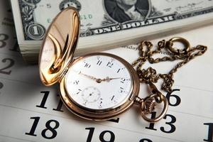 relógio de ouro e notas de dólar