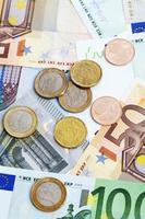 pilha de notas e moedas de euro foto