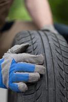 mãos mecânicas e pneu de carro foto