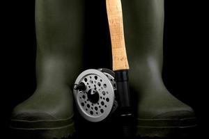 vara de pesca com mosca e molinete com fundo preto de botas vadear foto