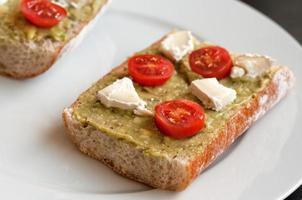 pão com propagação de abacate, queijo de cabra e tomate cereja foto