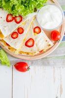fatias de quesadilla mexicana, servidas na placa de madeira com molho de iogurte
