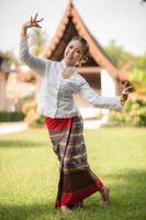 jovem mulher em trajes tradicionais, realizando uma dança cultural foto