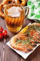 camarão grelhado, pretzel e caneca de cerveja foto