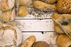 diferentes tipos de pão na placa de madeira branca foto