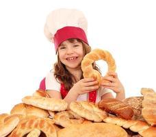 menina feliz cozinhar com pretzels pão e pãezinhos foto
