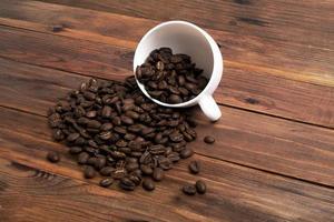 grãos de café e xícara em fundo madeira