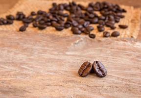 grãos de café no fundo da mesa de madeira foto