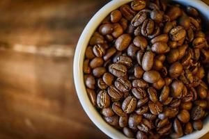 grãos de café na xícara em fundo de madeira grunge foto