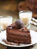 pedaço de bolo de chocolate com um café irlandês foto