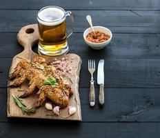 asas de frango frito na tábua rústica, molho de tomate picante foto