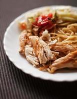 prato com carne e macarrão, salada, frango frito foto