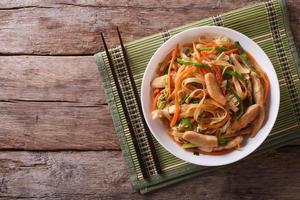 chow mein: macarrão frito com frango, vista superior horizontal foto