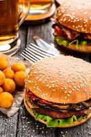 delicioso hambúrguer com bolas de batata frita e cerveja foto