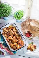 asas de frango picante com molho barbecue na cozinha rústica foto