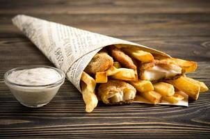 peixe e batatas fritas na mesa de madeira