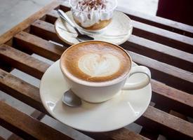 xícara de café com leite e sorvete na mesa do restaurante foto