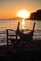 praia com pequeno diretor como cadeira ao pôr do sol em sithonia foto