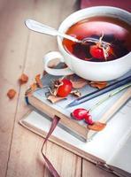 xícara de chá com rosas quadril e livros foto