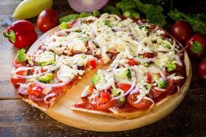 pizza na tábua de pizza de madeira foto