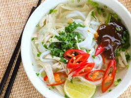 fotografia de sopa de macarrão de arroz de frango asiático com legumes
