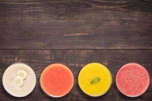 conjunto de smoothie da fruta e suco em copos na madeira foto