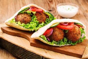 falafel e legumes frescos em pão pita na mesa de madeira foto