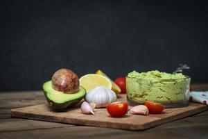 guacamole na mesa de madeira, rodeada por seus ingredientes foto