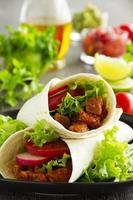 Burrito com carne de porco e tomate.