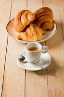café e croissants na mesa de madeira foto